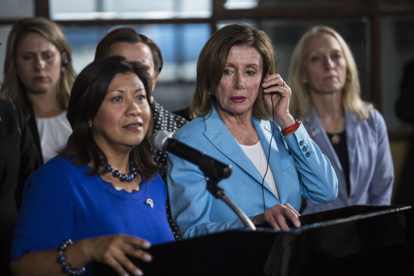 House Speaker Nancy Pelosi listens to Rep. Norma Torres speak at a news conference in Guatemala City.