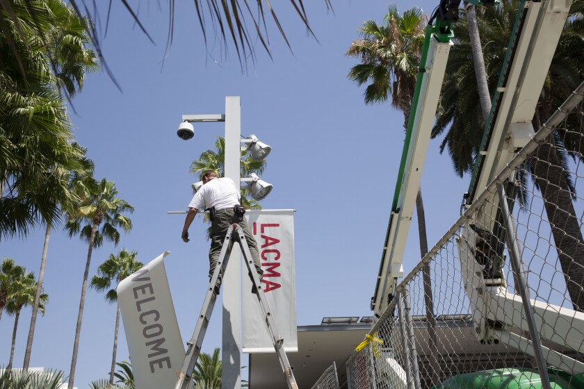 A worker takes down welcome banners at LACMA on Friday.