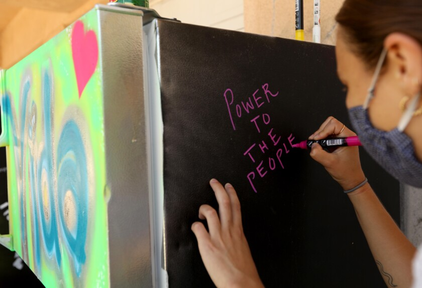 Emilia Shaffer-Del Valle writes a personal message on the Reach for the Top L.A. Mid-City Fridge