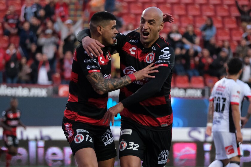 Tijuana Xolos forward Gustavo Bou (left) celebrates with fellow Argentine Ariel Nahuelpan after scoring earlier this season.