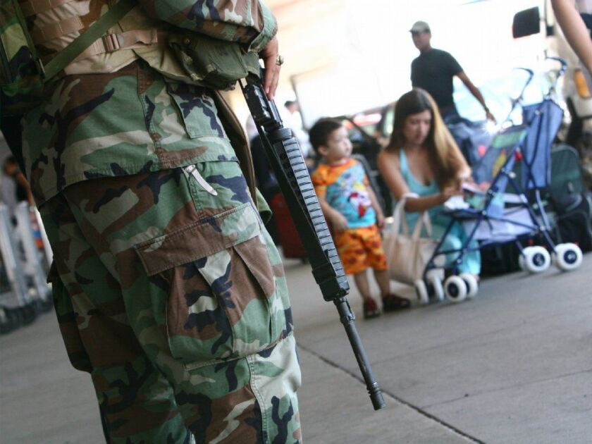 An M16 rifle hangs on the shoulder of National Guard Specialist Brian Sanchez as he makes his rounds outside American Airlines Terminal in JFK Airport in Queens to make is safer for passengers.