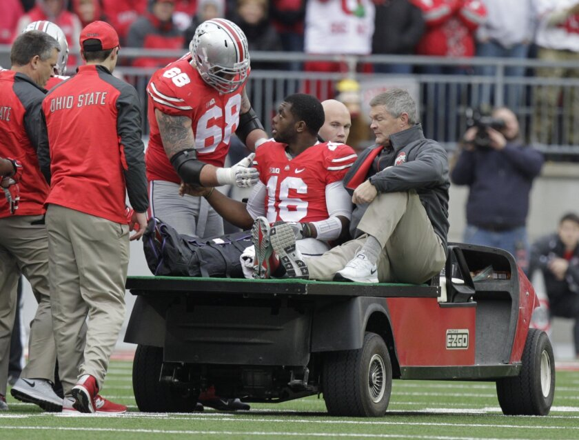 Ohio State offensive lineman Taylor Decker, left, talks with quarterback J.T. Barrett as Barrett is driven from the field after an injury during the fourth quarter of an NCAA college football game Saturday, Nov. 29, 2014, in Columbus, Ohio. Ohio State beat Michigan 42-28. (AP Photo/Jay LaPrete)
