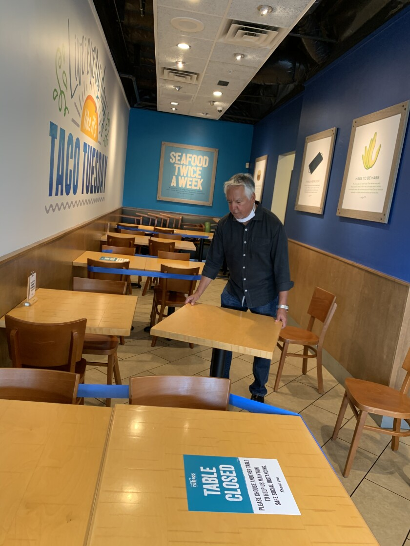 Rubio's co-founder Ralph Rubio moves tables as Rubio's restaurants implement strict social distancing procedures in preparation for re-opening their dining rooms on May 27.