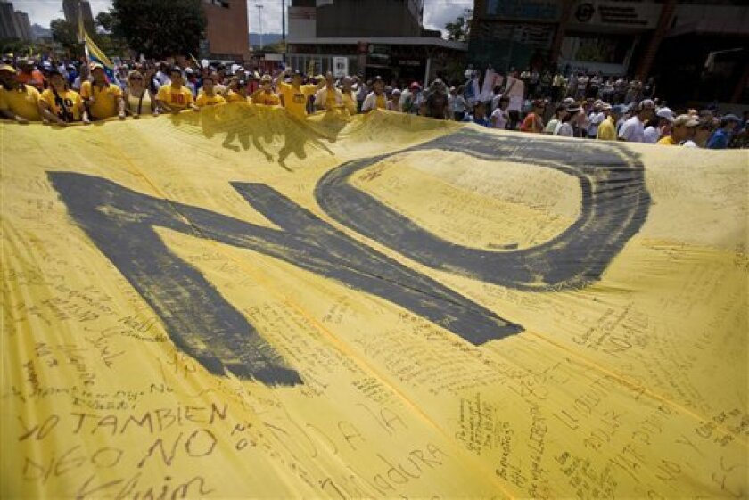 """Demonstrators carry a banner that reads """"No"""" to protest a constitutional amendment that would end term limits for elected officials in Caracas, Saturday, Feb. 7, 2009. The amendment, if approved in a referendum set for Feb. 15, could allow Venezuela's President Hugo Chavez and all other elected officials to run for re-election indefinitely. (AP Photo/Ariana Cubillos)"""