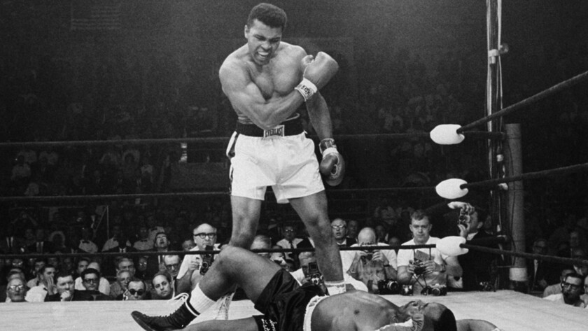 Heavyweight champion Muhammad Ali stands over fallen challenger Sonny Liston, shouting after knocking him down with a short, hard right to the jaw during their bout in Lewiston, Maine, on May 25, 1965.