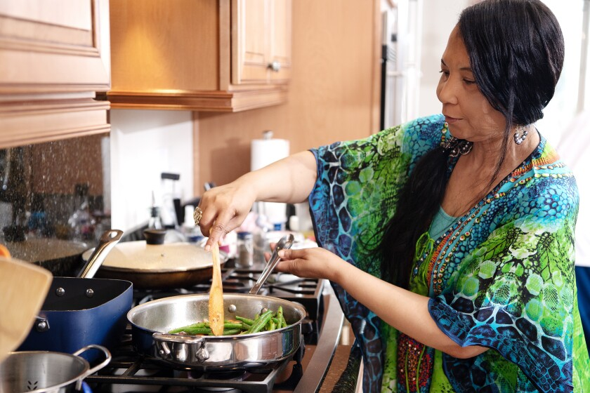 Chef Regina Mitchell stands at the stove stirring a vegetable dish with her right hand.