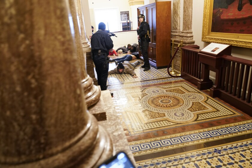 People lie on the floor of a Capitol hallway as police officers aim weapons