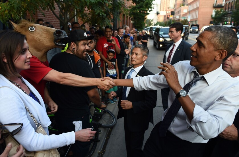 President Obama jokes around as he shakes hands with a man wearing a horse mask in Denver.