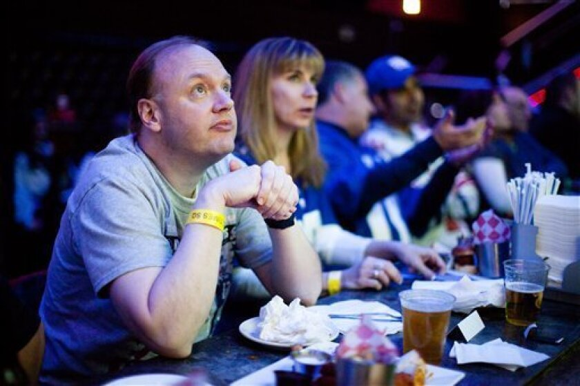 FILE - In this Feb. 5, 2012, file photo, Ron Blydenburgh, of Hampton Bays, N.Y., watches the broadcast of the 2012 NFL football Super Bowl. You don't have to be a football player to be a part of the action on Super Bowl Sunday, Feb 3, 2013. Coca-Cola is asking people to vote for an online match bet