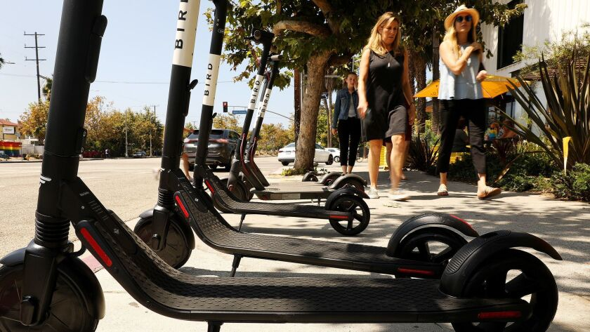 A row of electric scooters wait for customers near the corner of Abbot Kinney and Venice Boulevards in Venice, Calif. on August 15.