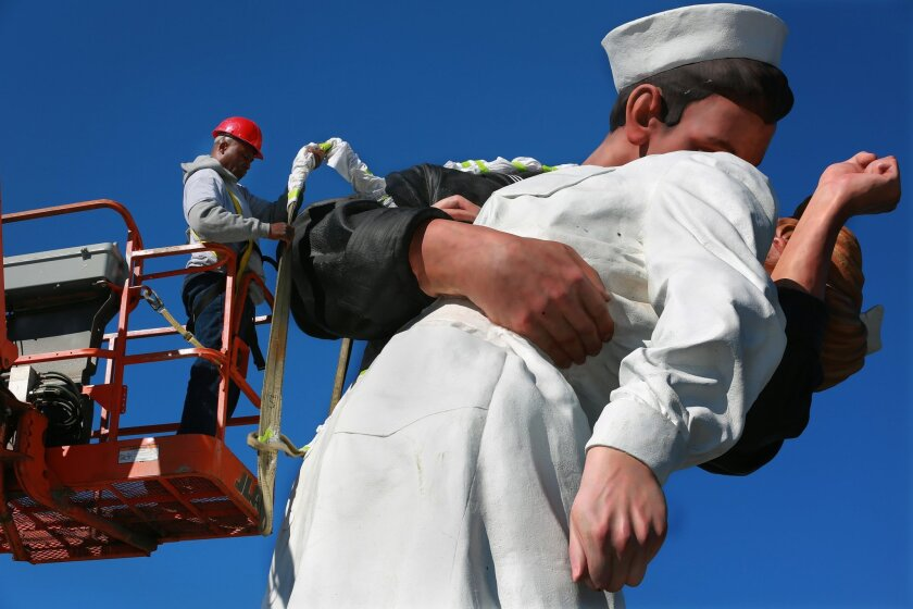 Autin Wright of the Sculpture Foundation untangles the statue from the wraps that carried it to its resting place Wednesday morning. The statue known as The Kiss was firmly installed in its new location Wednesday on the grassy knoll at G Street beside the Bob Hope Memorial in the shadow of the USS