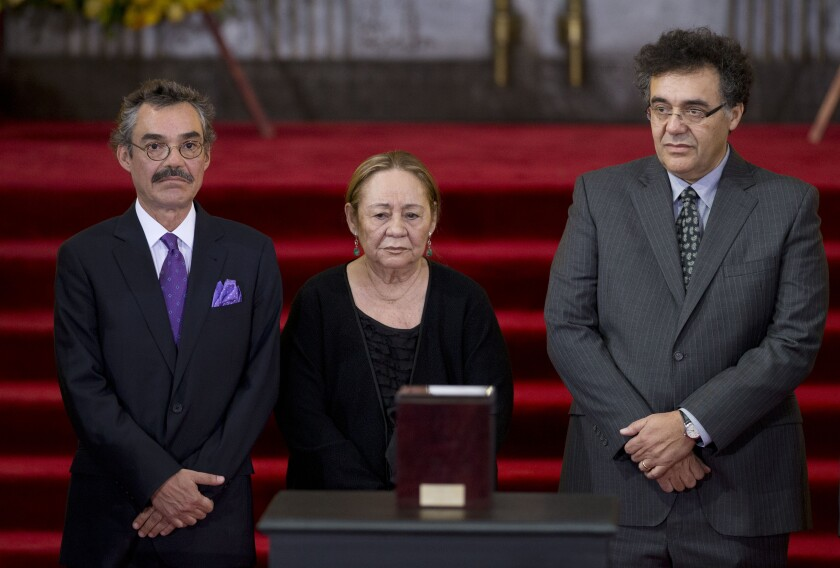FILE - In this April 21, 2014 file photo Mercedes Barcha, center, widow of Colombian Nobel Literature laureate Gabriel Garcia Marquez is accompanied by her sons Gonzalo, left, and Rodrigo as they stand next to the urn containing his ashes during an homage to Garcia Marquez in the Palace of Fine Art in Mexico City. Barcha died at the age of 87 at her home in Mexico City. (AP Photo/Rebecca Blackwell)