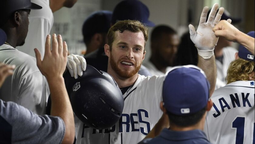The Padres' Cory Spangenberg is congratulated after scoring during the seventh inning of a baseball game against the Philadelphia Phillies at Petco Park on Aug. 11, 2018 in San Diego, California.