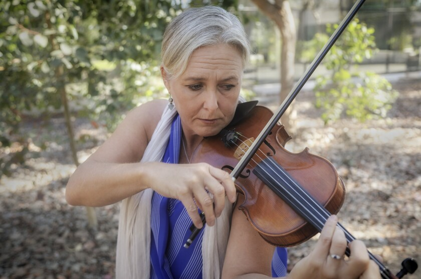 Violinist Healy Henderson performs at UCSD outside the La Jolla Playhouse.