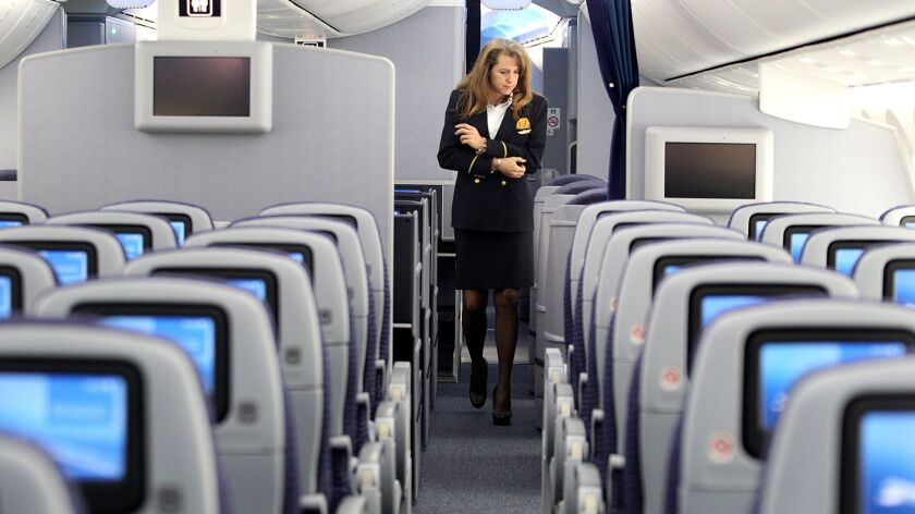 Flight attendant Tonya Johnson walks along the aisles of United Airlines' 787 Dreamliner at Los Angeles International Airport on Friday, Nov. 30, 2012. United flight attendants will begin Sept. 1 to pitch passengers on a co-branded credit card.