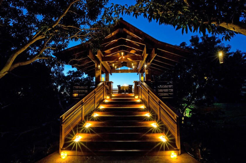 A wooden walkway leads to a romantic setting for a dinner for two in a treehouse amid avocado and mango trees on the grounds of Maui's Hotel Wailea.