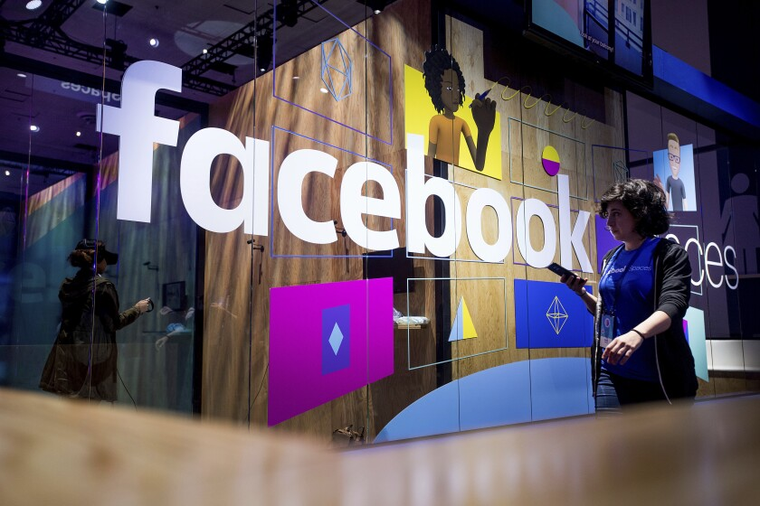 In this April 2017, photo, a conference worker passes a demo booth at Facebook's annual F8 developer conference in San Jose.