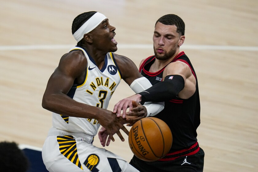 Indiana Pacers guard Aaron Holiday (3) is fouled by Chicago Bulls guard Zach LaVine during the first half of an NBA basketball game in Indianapolis, Tuesday, April 6, 2021. (AP Photo/Michael Conroy)