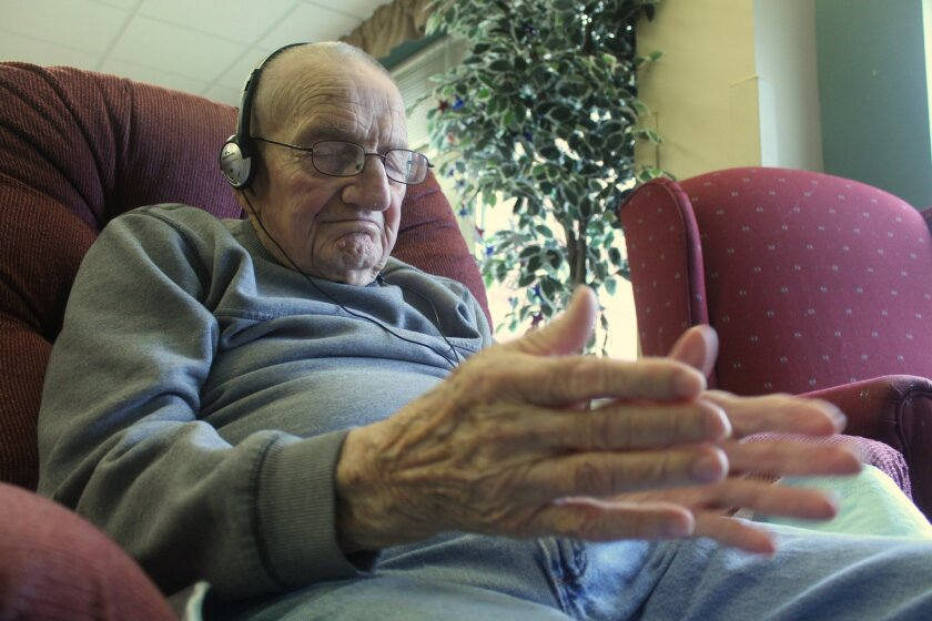 In this photo taken Sept. 4, 2014, in Union Grove, Wis., Mike Knutson, 96, claps his hands as he listens to music on an iPod. He is part of a study through the University of Wisconsin-Milwaukee that is looking at whether mood and behavior is altered when dementia and Alzheimer's patients listen to