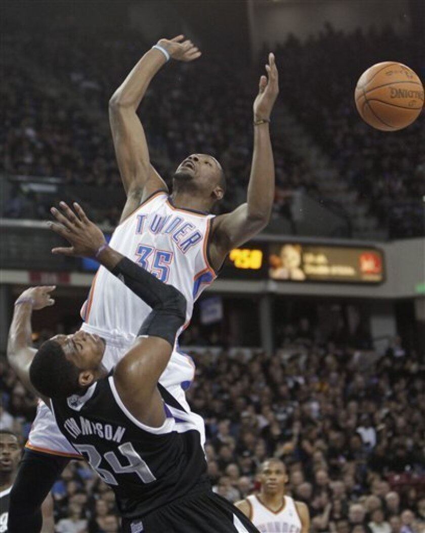 Sacramento Kings forward Jason Thompson, left, tries to stop Oklahoma City Thunder forward Kevin Durant's drive to the basket during the first quarter of an NBA basketball game in Sacramento, Calif., Thursday, Feb. 9, 2012. Thompson was called for a foul. (AP Photo/Rich Pedroncelli)