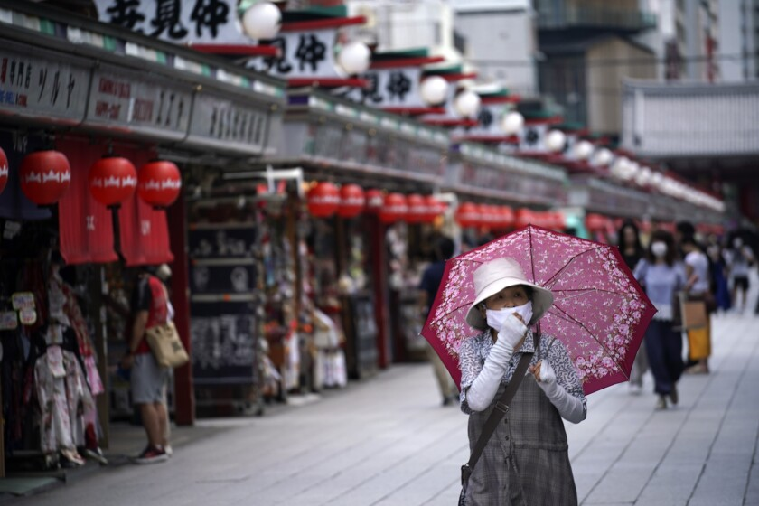 People walk through a shopping arcade near Sensoji Temple in Tokyo Friday, June 12, 2020. (AP Photo/Eugene Hoshiko)