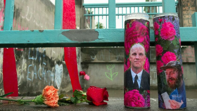 Candles bearing photos of two stabbing victims sit at a memorial in Portland. A photo of Ricky Best,