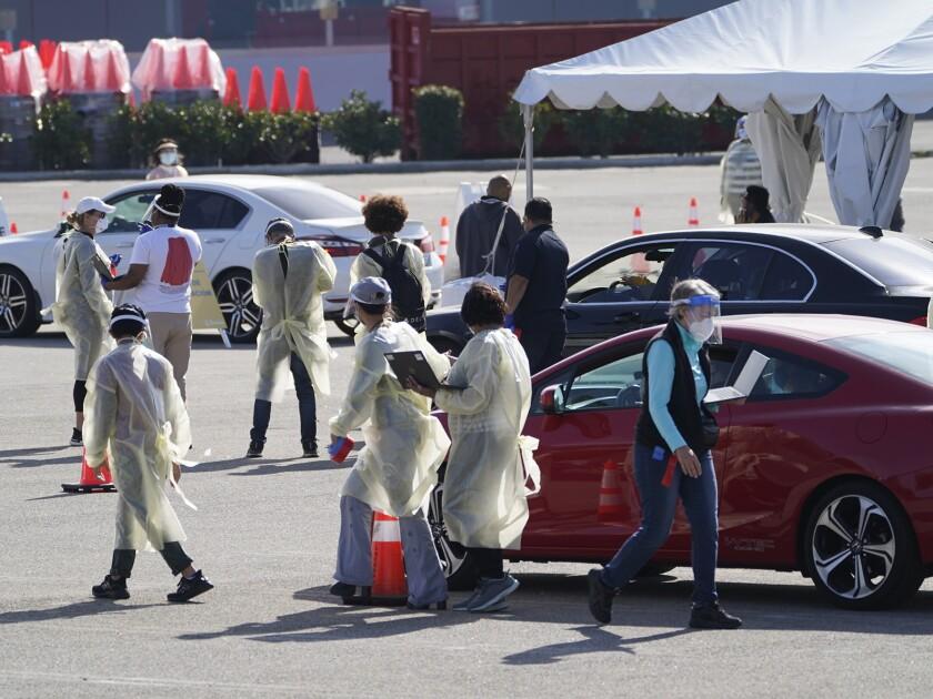 Personas aguardan dentro de sus vehículos en fila en un sitio de vacunación contra el COVID-19