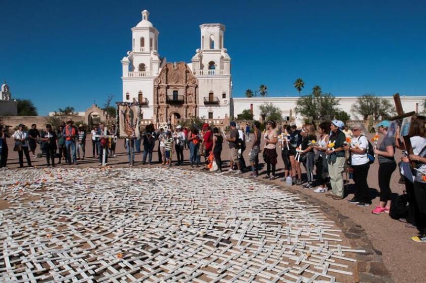 Varias personas participan en una caminata para recordar a los inmigrantes indocumentados fallecidos en el desierto de Arizona, el sábado 31 de octubre de 2015, en Tucson, Arizona (EE.UU.). Cargando cruces de color blanco adornadas con flores de colores, decenas de personas caminaron hoy por las calles del sur de Tucson para recordar a los inmigrantes indocumentados fallecidos en el desierto de Arizona.