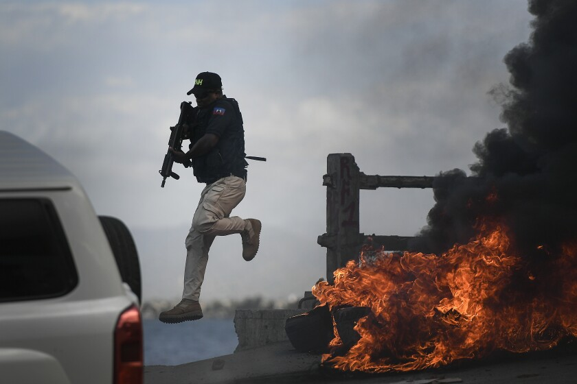 A police officer leaps from his vehicle alongside a burning roadside