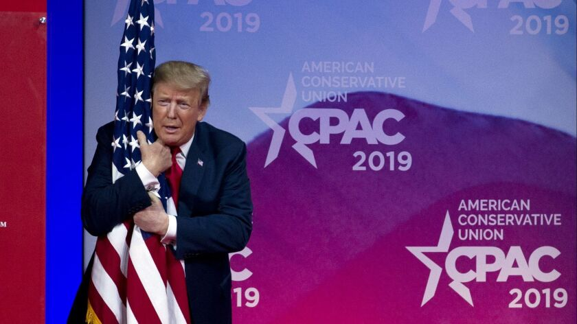 President Trump hugs a U.S. flag as he arrives to speak at the Conservative Political Action Conference on March 2, 2019.