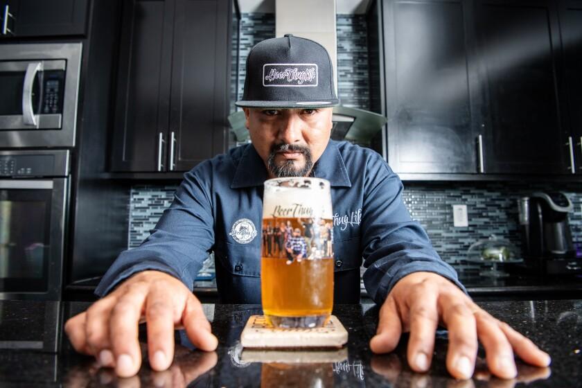 Edgar Preciado looking at a glass of beer.