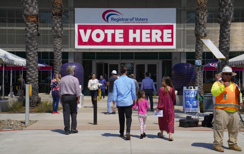 Los votantes llegan a la oficina del Registro de Votantes en Kearny Mesa para emitir su voto.