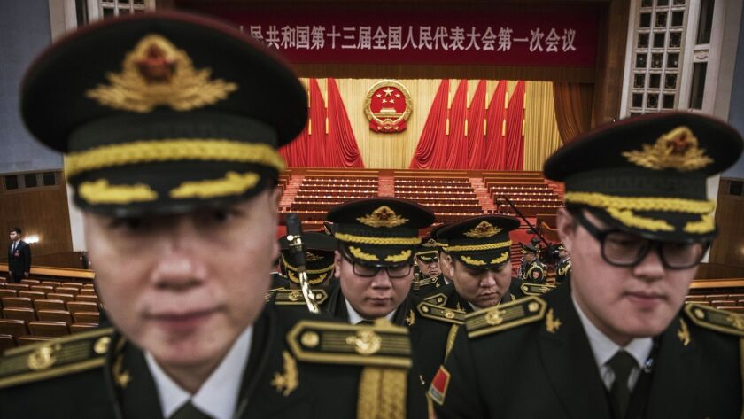 Members of a band from the People's Liberation Army leave following a speech by Chinese President Xi Jinping after the closing session of the National People's Congress in Beijing on March 20, 2018.