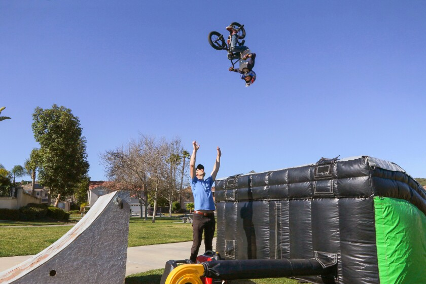At a park near their home in San Marcos on Saturday, Feb. 29, John Stitt, 35, watches his 9-year-old son, Connor, do an aerial back flip on his BMX bike while flying off the wooden kicker jump that John made, at left. He's about to land on an inflated landing ramp.