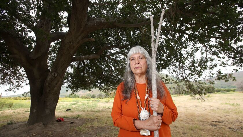 """Spiritual leader Adelia Sandoval stands proudly next to the """"mother oak,"""" central to the Juaneno Mis"""