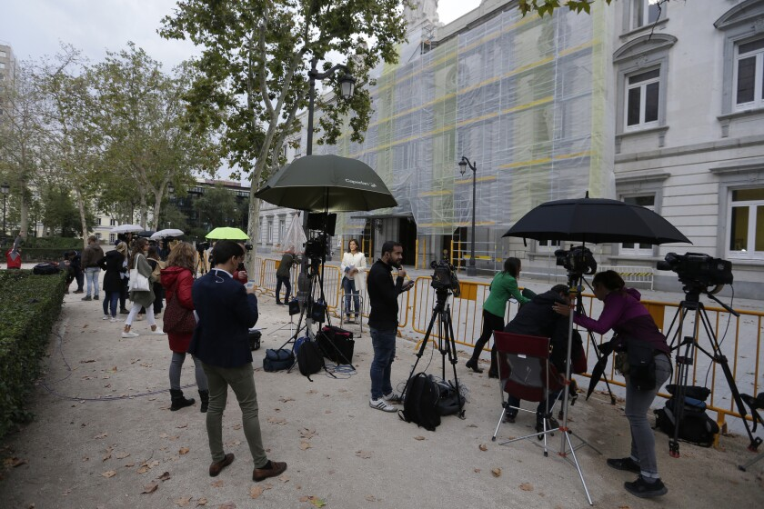 Journalists wait outside the Supreme Court in Madrid, Spain, Monday, Oct. 14, 2019. Spain's Supreme Court is set to rule on a rebellion and sedition trial against a dozen Catalan politicians and activists who were key protagonists in Catalonia's Oct. 1, 2017, independence referendum. (AP Photo/Paul White)