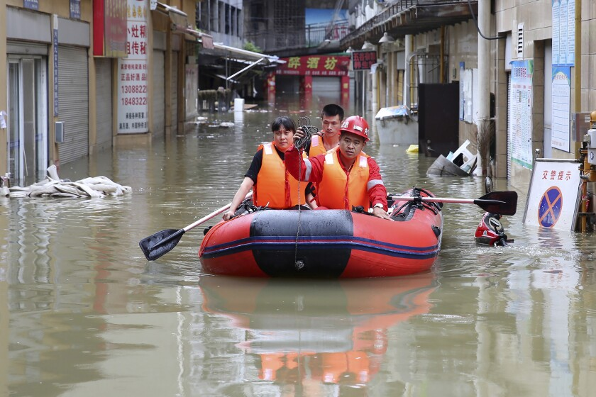 Rescuers use an inflatable boat as they evacuate people from a flooded neighborhood in Neijiang in southwestern China's Sichuan Province, Tuesday, Aug. 18, 2020. Authorities deployed helicopters in western China to rescue people stranded by flooding as heavy rain swelled rivers to dangerous levels, state media reported. (Chinatopix via AP)