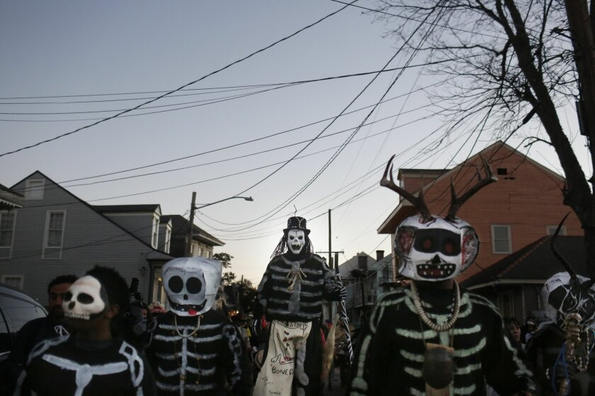 The North Side Skull & Bone Gang parade down the streets during the wake up call for Mardi Gras, Tuesday, Feb. 9, 2016, in New Orleans. Their costumes are intended to represent the dead and they bring a serious message, reminding people of their mortality and the need to live a productive and good