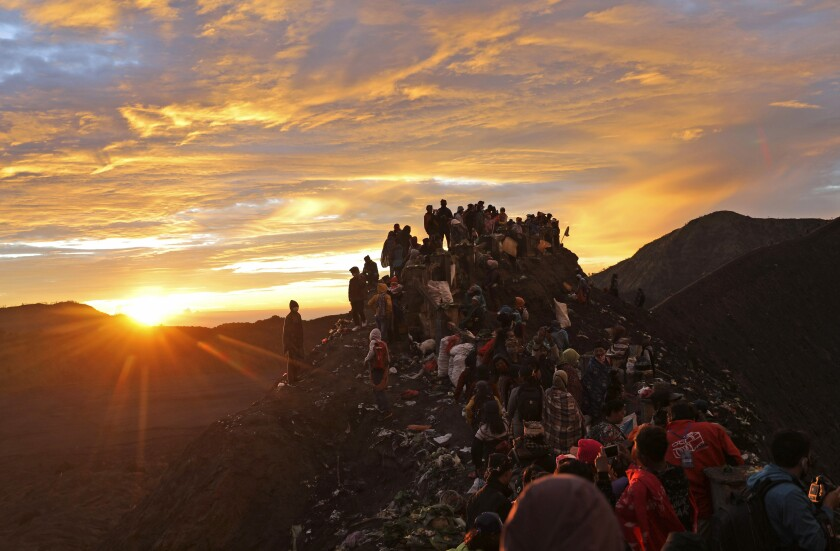 Hindu devotees and visitors make their way to the top of of Mount Bromo at dawn during the Yadnya Kasada festival in Probolinggo, East Java, Indonesia, Tuesday, July 7, 2020. Every year people gather at the active volcano to make offerings of rice, fruit, vegetables, livestock or money to Hindu gods to ask for blessings and assure a bountiful harvest. (AP Photo/Trisnadi)