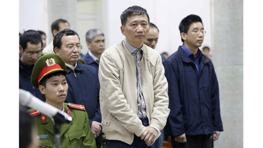 Trinh Xuan Thanh, center, listens during his embezzlement trial in Hanoi. Prosecutors are seeking life imprisonment for Thanh, the former chairman of a construction company tied to state energy giant PetroVietnam.