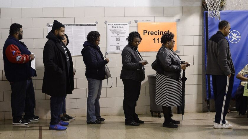 FILE- In a Nov. 6, 2018 file photo voters wait in line on election day in Southfield, Mich. A three-