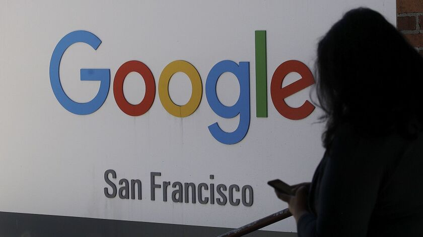 FILE - In this May 1, 2019, file photo, a woman walks past a Google sign in San Francisco. The U.S.