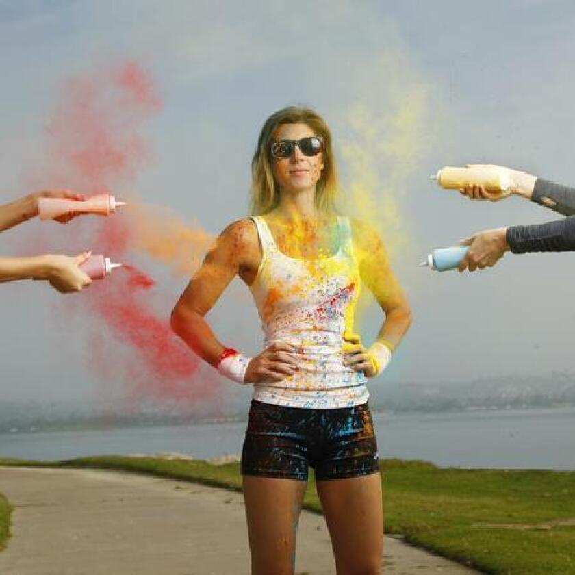 Model Nicole Zuelke stood patiently while being peppered with colored powder for the fun run photo shoot. (K.C. Alfred)