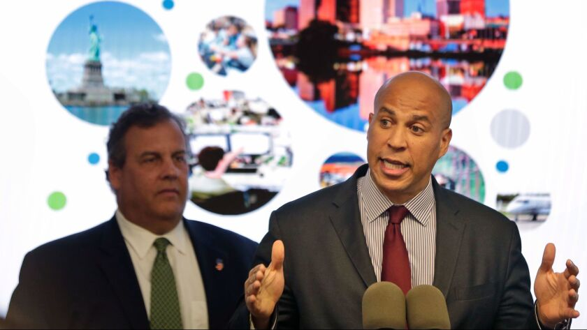 New Jersey Sen. Cory Booker, right, speaks while New Jersey Gov. Chris Christie stands behind him in Newark, N.J. on Oct. 16. The New Jersey lawmakers announced they are submitting a bid to Amazon that Newark would be the best location for their planned second headquarters.
