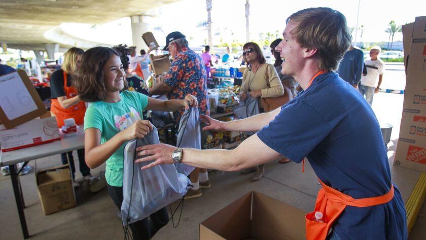 SAN DIEGO, November 10, 2018 | Bella Bosmer, 10, hands Andrew Kasselmann her bags filled with food i