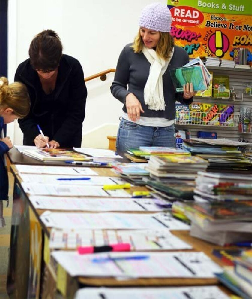 Parents and children look over their teachers' wish lists. Photo: Pearl Preis