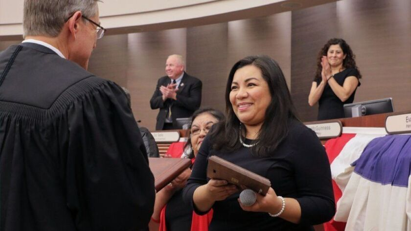 Incoming Escondido Councilwoman Consuelo Martinez smiles after being sworn into office Wednesday by Honorable Judge Sim von Kalinowski. Applauding in the distance are new Mayor Paul McNamara and Councilwoman Olga Diaz.