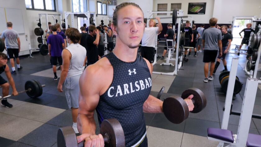 Carlsbad High School football player Asa Turner works out in the weight room with his teammates.