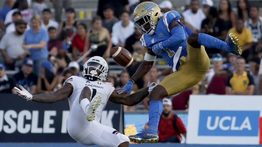 UCLA defensive back Darnay Holmes breaks up a pass intended for Cincinnati wide receiver Kahlil Lewis at the Rose Bowl on Sept. 1.