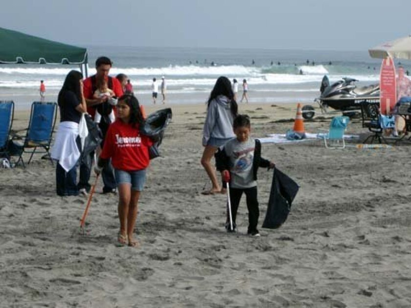 Children of Jerome's employees help clean up the beach. Photo: Courtesy
